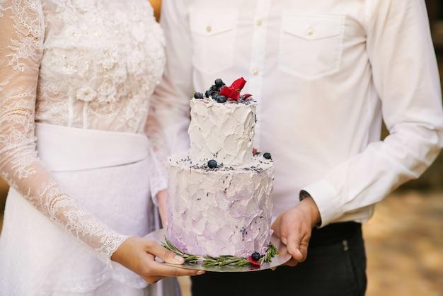 Mooie bruidstaart met bloemen op de achtergrond van pasgetrouwden