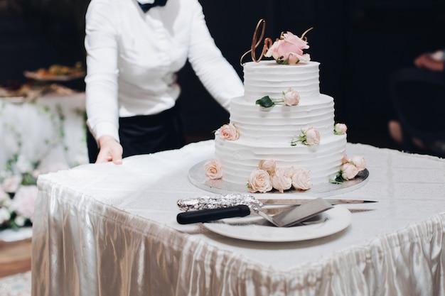 Mooie bruidstaart met bloemen op tafel