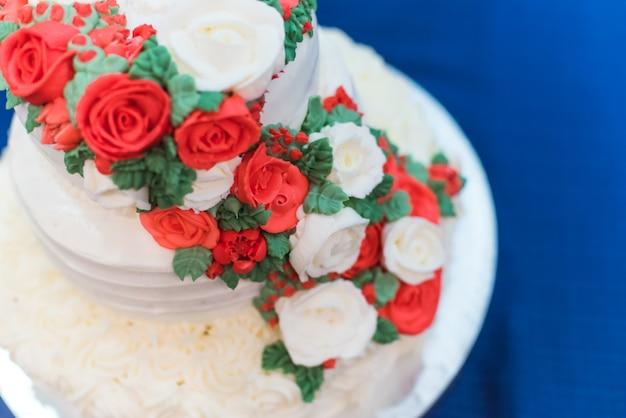 Mooie bruidstaart met rode roos bloemen decoratie.