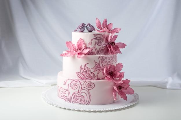 Mooie bruidstaart versierd met roze bloemen
