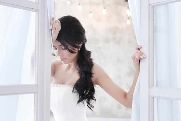 Mooie bruidvrouw die in huwelijkskleding een boeket van bloemen houdt