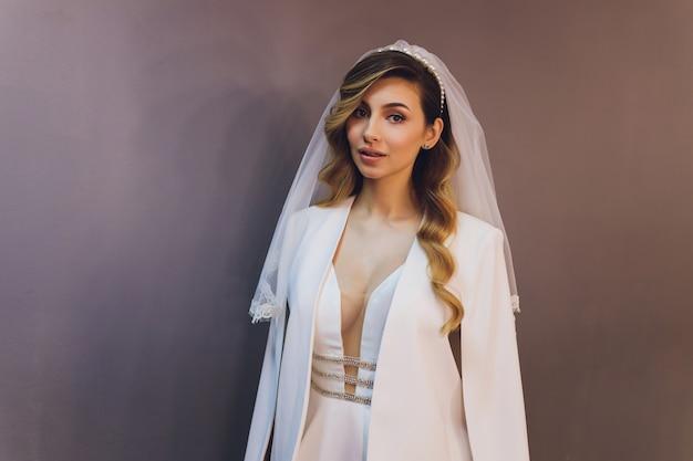 Mooie bruidvrouw in huwelijkskleding en sluier. mode portret van jonge prachtige bruid. trouwjurk.