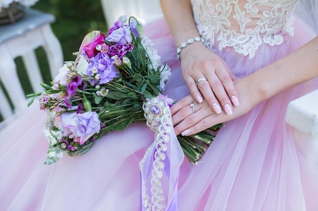 Mooie bruiloft kleurrijk boeket met verschillende bloemen in de handen van de bruid. bruids zomerboeket