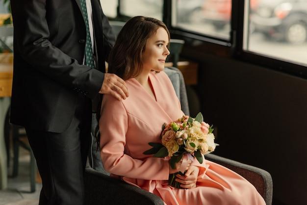Mooie bruiloft, man en vrouw, bruid en bruidegom in loft interieur in de buurt van raam. pasgetrouwden verliefde paar. bruidegom knuffel de bruid.