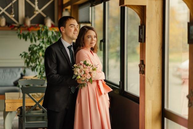 Mooie bruiloft, man en vrouw, bruid en bruidegom staan in loft interieur in de buurt van raam. pasgetrouwden verliefde paar. bruidegom knuffel de bruid bij de schouders. de bruidegom houdt een huwelijksboeket in handen.