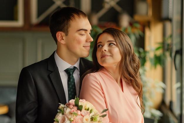 Mooie bruiloft, man en vrouw, bruid en bruidegom staan in loft interieur in de buurt van raam. pasgetrouwden verliefde paar. bruidegom knuffel de bruid bij de schouders.