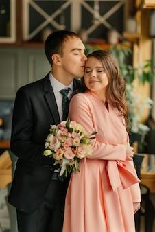 Mooie bruiloft, man en vrouw, bruid en bruidegom staan in loft interieur in de buurt van raam. pasgetrouwden verliefde paar. bruidegom knuffel de bruid en kus. de bruidegom houdt een huwelijksboeket in handen.