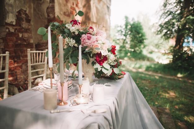 Mooie bruiloftstafel met kaarsen in de tuin. vakanties en evenementen
