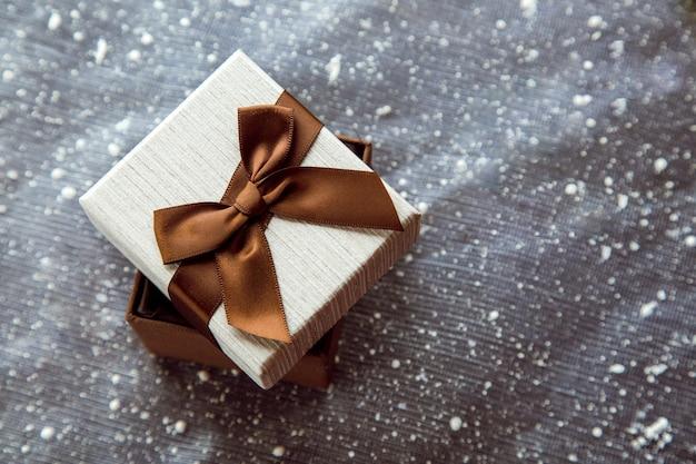 Mooie bruine geschenkdoos met witte omslag een idee voor een cadeau op kerstmis vrije ruimte voor tekst