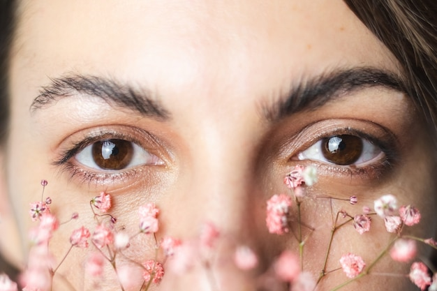 Mooie bruine vrouwenogen en dikke perfecte wenkbrauwen met schattige kleine gedroogde bloemen onder de ogen