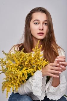 Mooie bruinharige vrouw met gele mimosa bloemen op een witte achtergrond. lente portret van een meisje