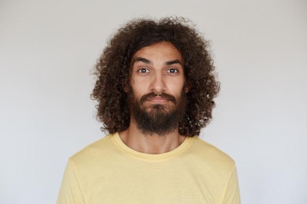 Mooie bruinogige donkerharige krullende man met baard, gekleed in een geel t-shirt, op zoek met een kalm gezicht