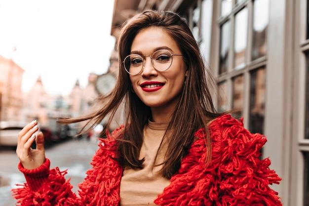 Mooie bruinogige vrouw in glazen raakt koket haar haar. vrouw met rode lippenstift in heldere gebreide outfit en hoofdtooi loopt door de stad.
