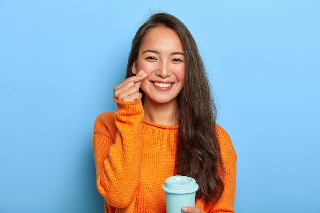 Mooie brunette asain duizendjarige vrouw houdt afhaalmaaltijden koffiekopje, geniet van een drankje tijdens de pauze, draagt een warme oranje trui