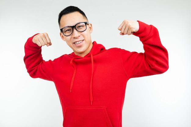 Mooie brunette aziatische in rode trui en bril voor visie vormt op een wit