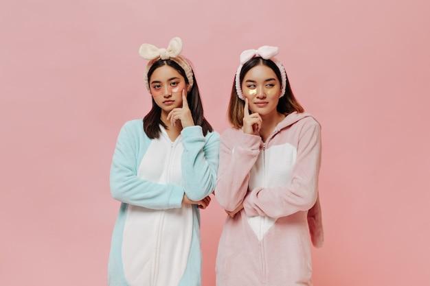 Mooie brunette aziatische meisjes in kigurumi's kijken bedachtzaam