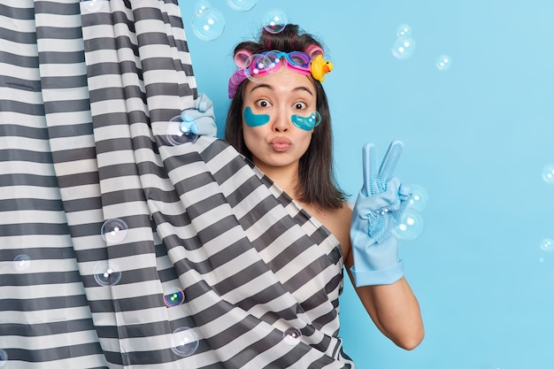 Mooie brunette aziatische vrouw brengt collageenpleisters aan terwijl ze een douche neemt en maakt een vredesgebaar schoonheidsprocedures ondergaat zich achter douchegordijn poses tegen blauwe muur zeepbellen rond