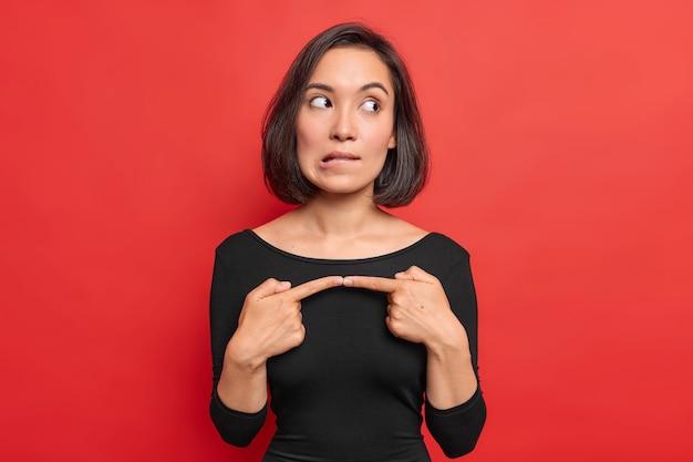 Mooie brunette aziatische vrouw heeft aarzelende uitdrukking en maakt voor mij een gebaar dat besluiteloos voelt voordat ze iets belangrijks doet, bijt lippen draagt zwarte trui geïsoleerd over levendige rode muur