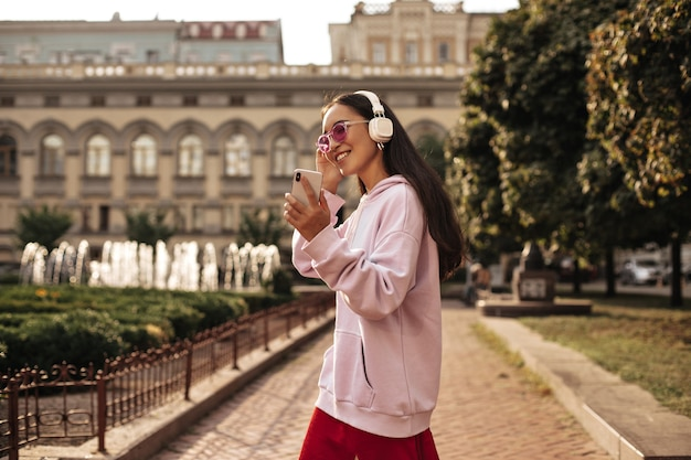 Mooie brunette aziatische vrouw in roze zonnebril houdt telefoon vast, glimlacht, luistert naar muziek in koptelefoon