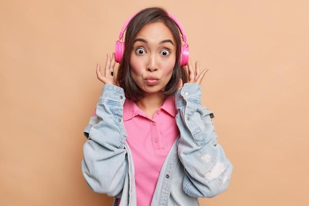 Mooie brunette aziatische vrouw met donker haar houdt lippen gevouwen heeft geschokte uitdrukking luistert muziek via roze draadloze koptelefoon draagt spijkerjasje geïsoleerd over beige muur