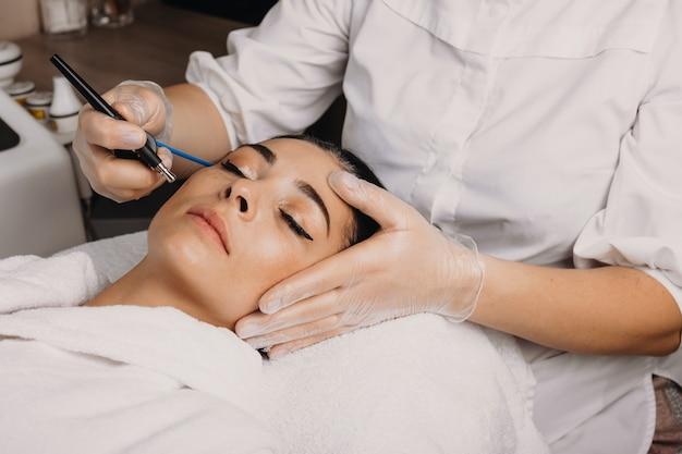 Mooie brunette blanke vrouw liggend met gesloten ogen op de bank terwijl het hebben van een spa-procedure voor haar gezicht