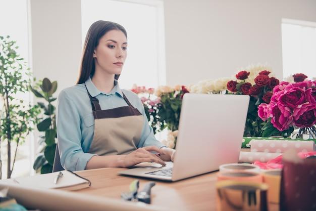 Mooie brunette botanicus poseren in haar bloemenwinkel met laptop