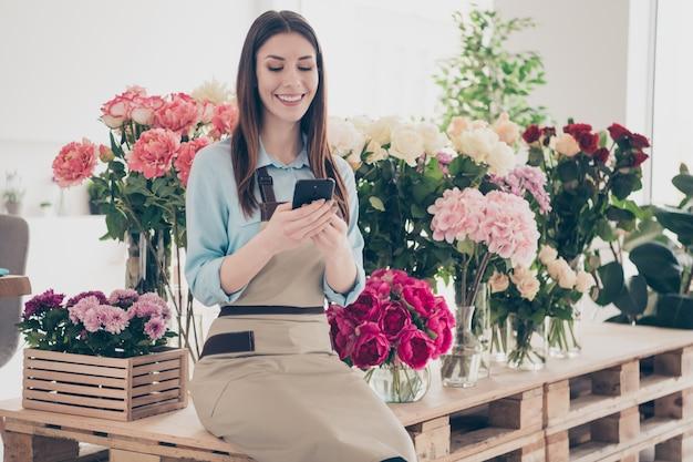 Mooie brunette botanicus poseren in haar bloemenwinkel met telefoon