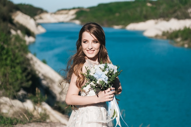 Mooie brunette bruid in witte trouwjurk met grote lange witte trein en met bruiloft boeket staan op de rand van een klif en een blauw meer.