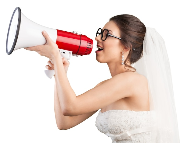 Mooie brunette bruid in witte trouwjurk met megafoon op witte achtergrond