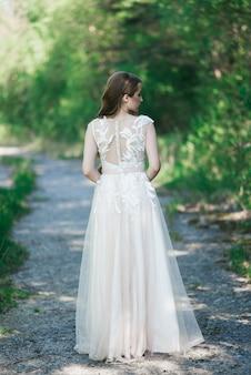 Mooie brunette bruid met krullen, make-up en stijlvolle jurk. portret op de muur van groene bomen. zomer trouwdag.