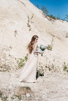 Mooie brunette bruid met vliegende krullen op de achtergrond van een zanderige berg in een stijlvolle jurk en een blauw en wit boeket.