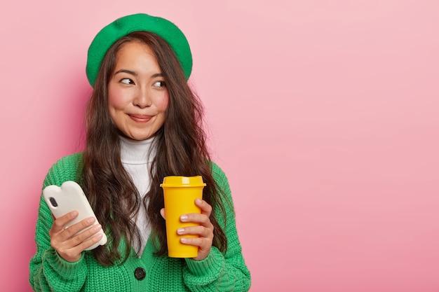 Mooie brunette dame in groene outfit, houdt mobiele telefoon in de ene hand en koffiekopje in andere looks met dromerige gezichtsuitdrukking