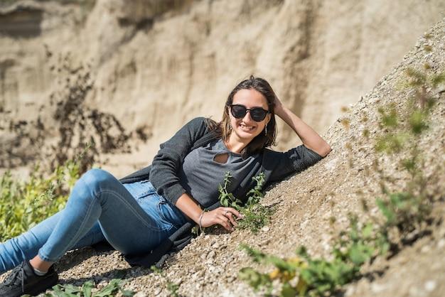 Mooie brunette dame in zandgroeve ontspannen en genieten van haar tijd op zonnige zomerdag