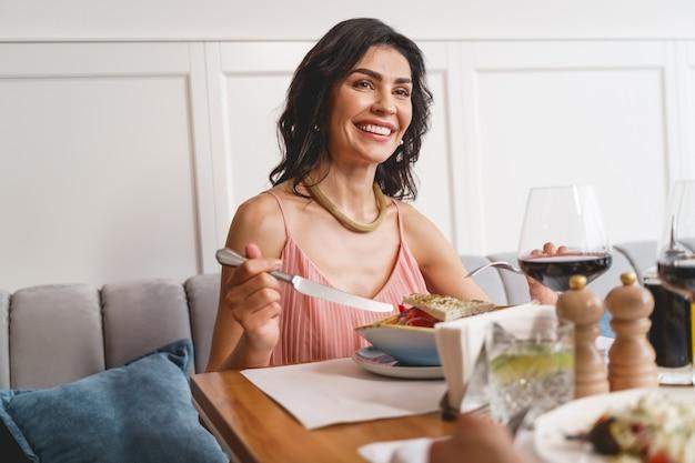 Mooie brunette dame zit aan tafel met heerlijk eten en lacht