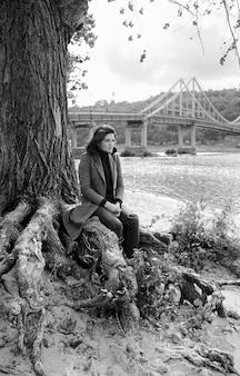 Mooie brunette depressieve trieste vrouw bij de rivier in de stad op de achtergrond van de brug