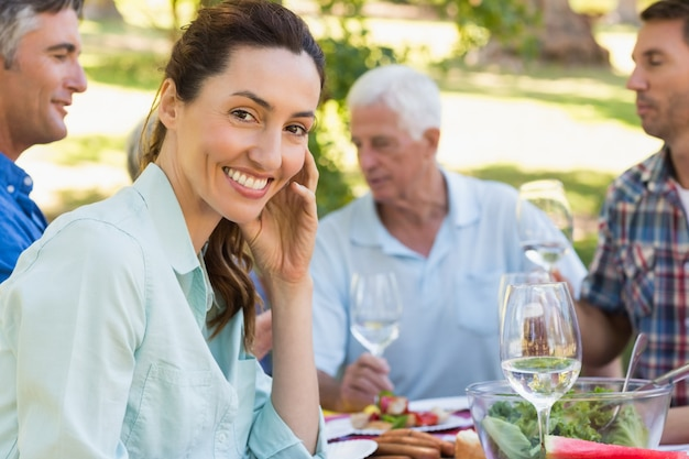 Mooie brunette die bij camera tijdens een picknick glimlacht