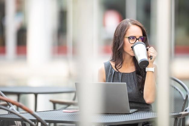 Mooie brunette die buiten koffie drinkt van een duurzame koffiemok terwijl ze op de laptop werkt in een kantooromgeving.