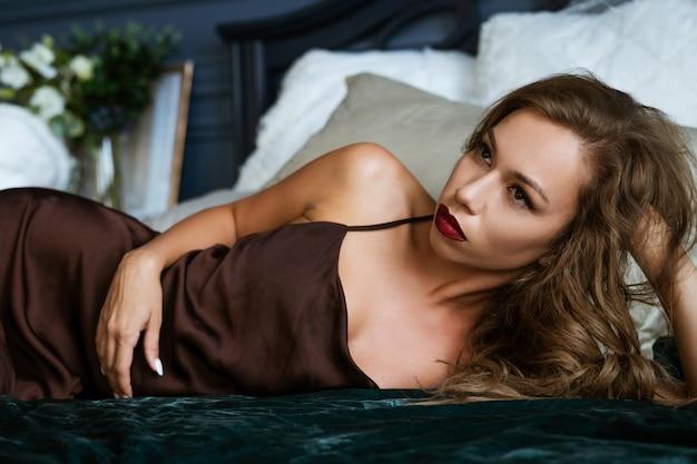 Mooie brunette die op het bed, donkere foto ligt