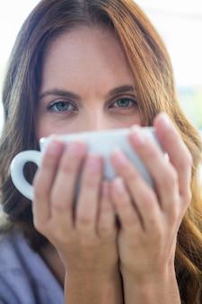 Mooie brunette die van een cappuccino geniet