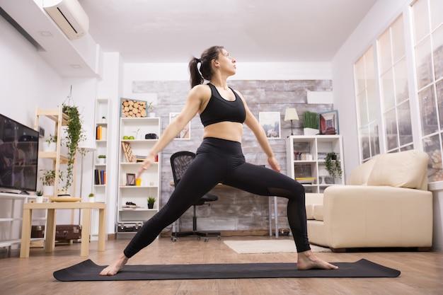 Mooie brunette die zich in de positie van de strijdersyoga bevindt die zwarte sportkleding in woonkamer draagt.