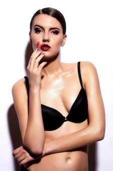 Mooie brunette die zich voordeed op lingerie verspreid lippenstift