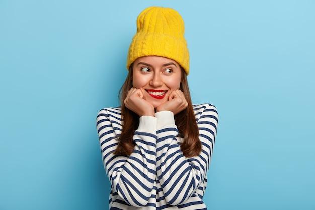 Mooie brunette duizendjarige vrouw houdt handen onder de kin, bijt op de lippen, heeft tevreden uitdrukking, draagt gele hoed en gestreepte trui