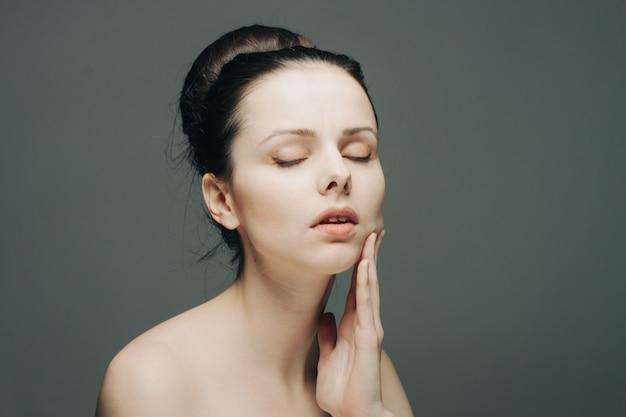 Mooie brunette emoties naakt schouder hand op gezicht luxe