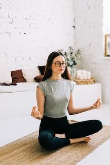 Mooie brunette fitness vrouw mediteren doet yoga binnenshuis thuis