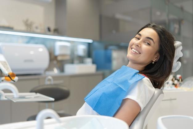 Mooie brunette gelukkige vrouwelijke patiënt zittend in de stoel bij tandheelkundige kliniek.