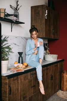 Mooie brunette in blauwe pyjama zittend op het aanrecht met mok koffie op kerstochtend.