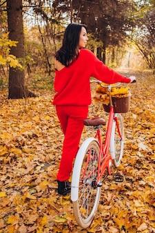 Mooie brunette in de herfst bos met een fiets