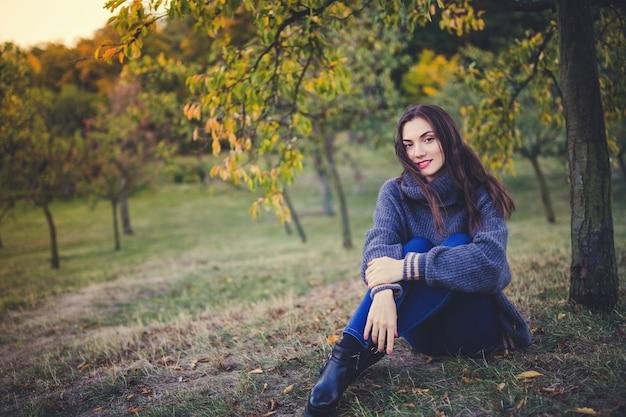 Mooie brunette in een gebreide trui zittend onder de boom in een herfst park