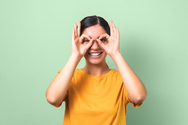 Mooie brunette in gele t-shirt die glazen van haar vingers maakt en grappig glimlachend gezicht tegen groene achtergrond