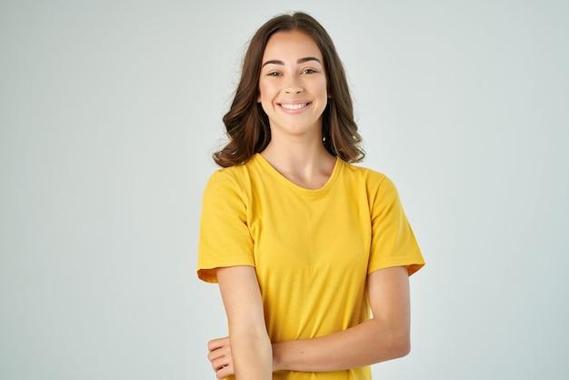 Mooie brunette in gele tshirt glimlach poseren levensstijl